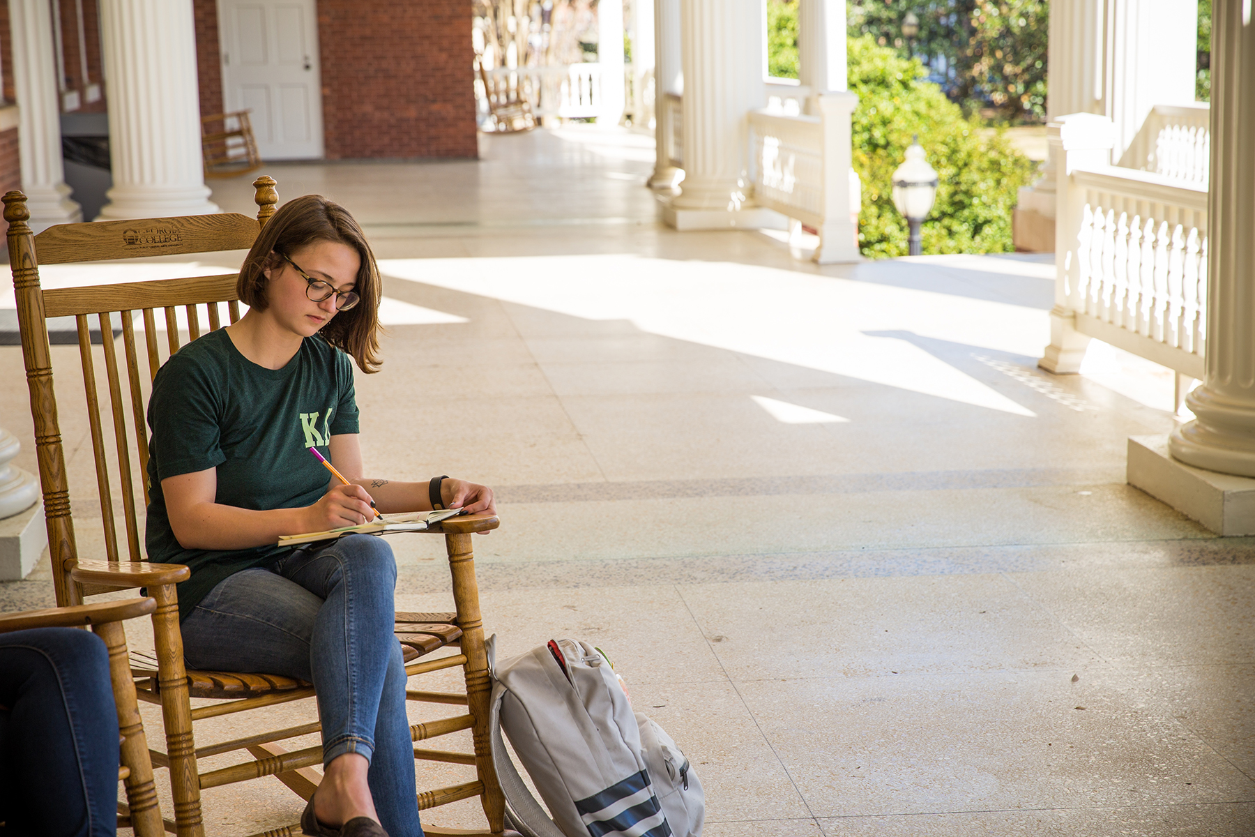 a college-aged girl sitting in a rocking chair on a porch, journaling