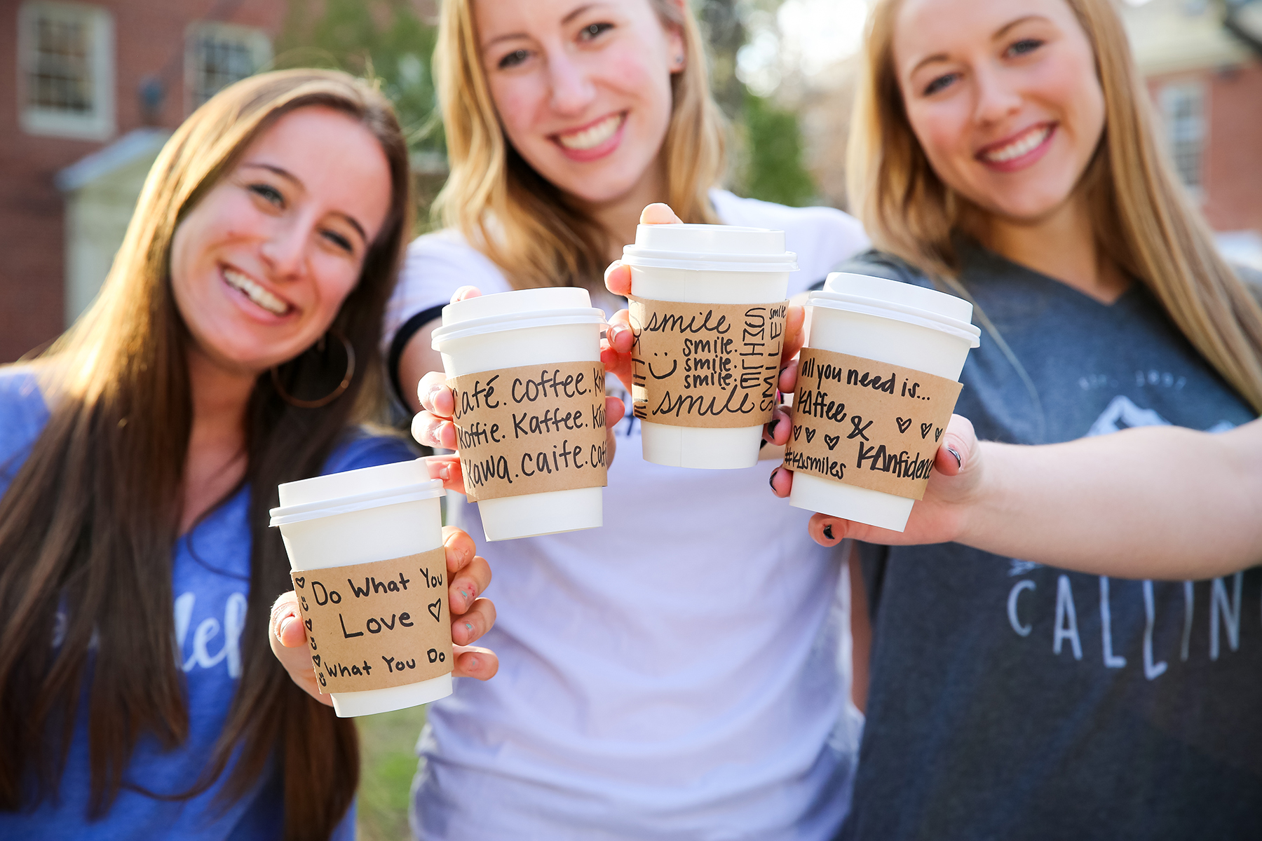 three smiling girls holding to go coffee cups with compliments written on them