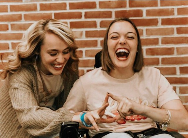 women laughing in front of brick wall