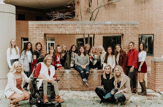 group photo of college women by brick building