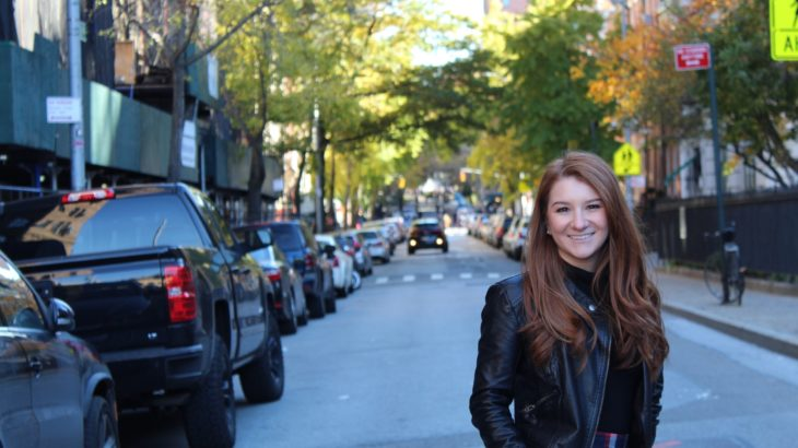 women with red hair stands outside in street