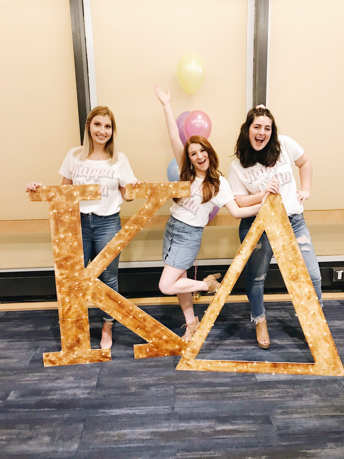 three women stand with sorority letters
