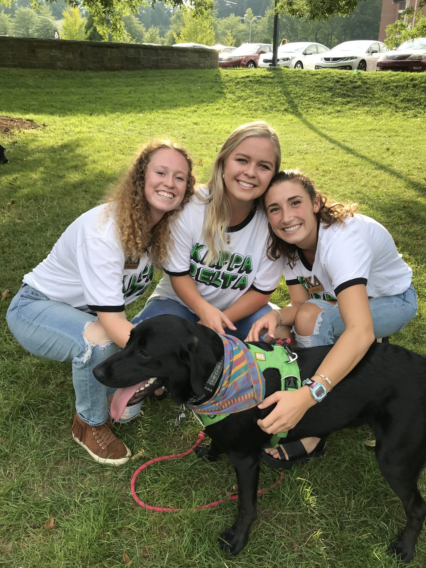 women in matching shirts with a dog outside