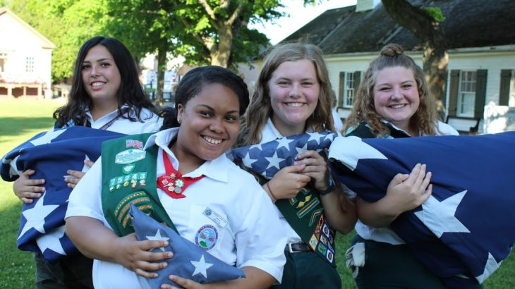 girl scouts holding american flag