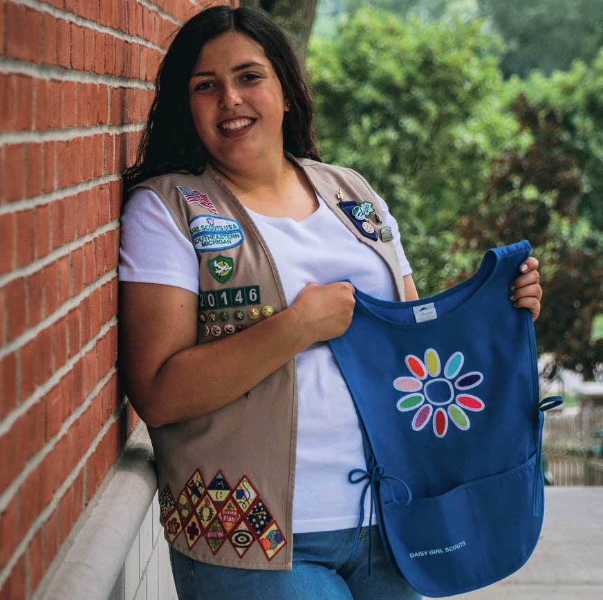 girl scout holding badges